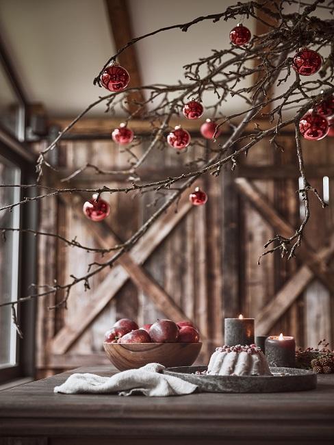 Ast dekorieren mit roten Weihnachtskugeln