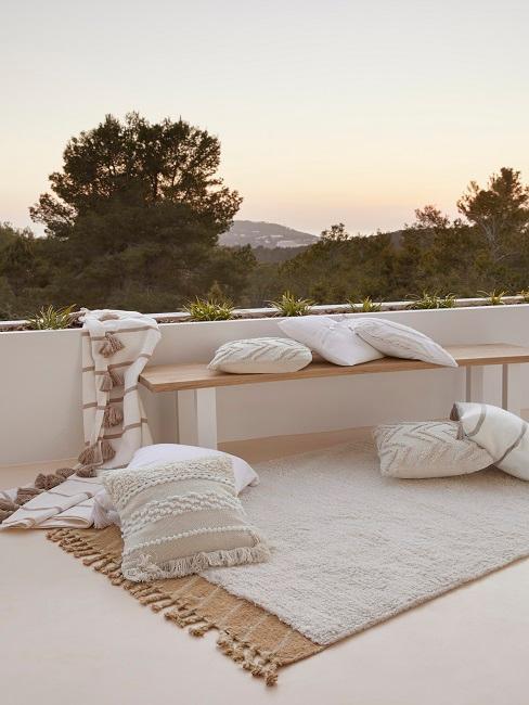 EIne Terrasse mit zwei hellen Teppichen, einer Holzbank und hellen Deko Kissen im Bohemian Style