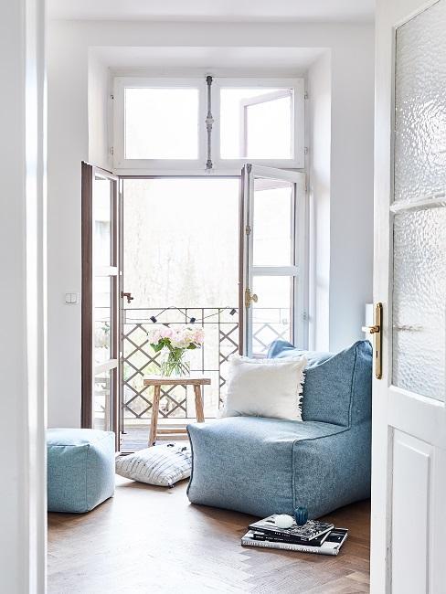 Helles Wohnzimmer mit einem cozy Sessel mit Kissen, einem Pouf und Büchern vor der offenen Balkontüre