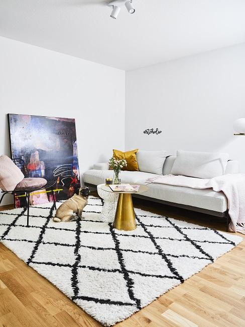 Wohnzimmer mit hellem Sofa, einem gemusterten Teppich und einem Couchtisch