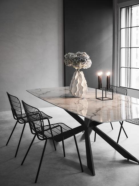 Luxus Wohnung einrichten Esszimmer mit Mamortisch, schwarzen Stühlen, Kerzen und Blumenvase