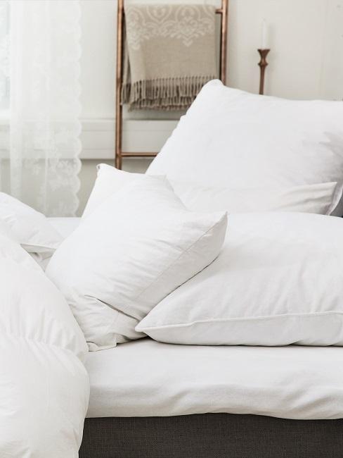 Ein Bett mit strahlend frischer Bettdecke in Weiß und mehreren Kissen
