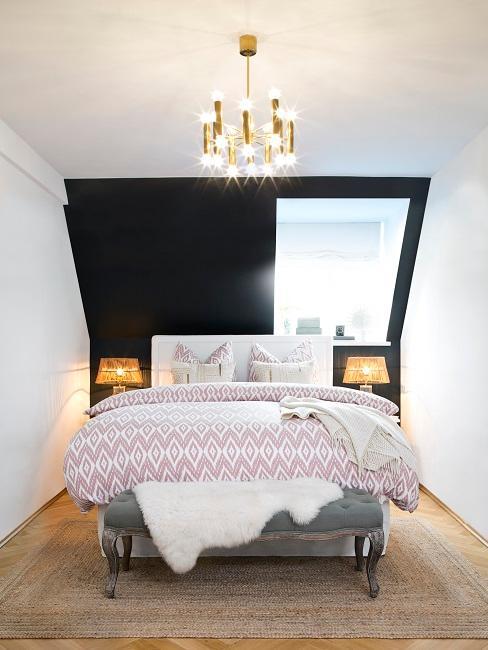 Bett mit bunterbettwäsche, die Wand hinter dem Bettkopf ist schwarz gestrichen