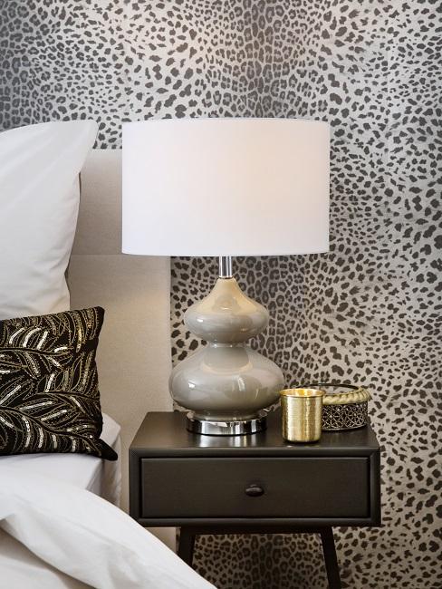 Helles Bett vor einer Wand mit Tapete im Leopardenmuster