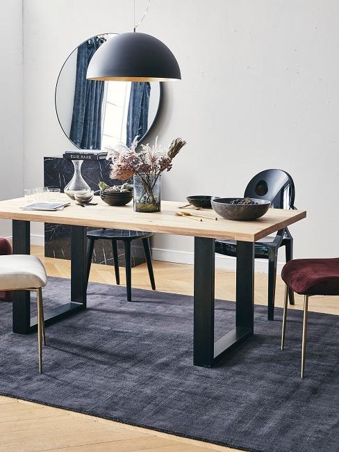 Esszimmer mit einem grafisch geformten Tisch aus Holz auf dunklem Teppich und mit minimalistischer Deko