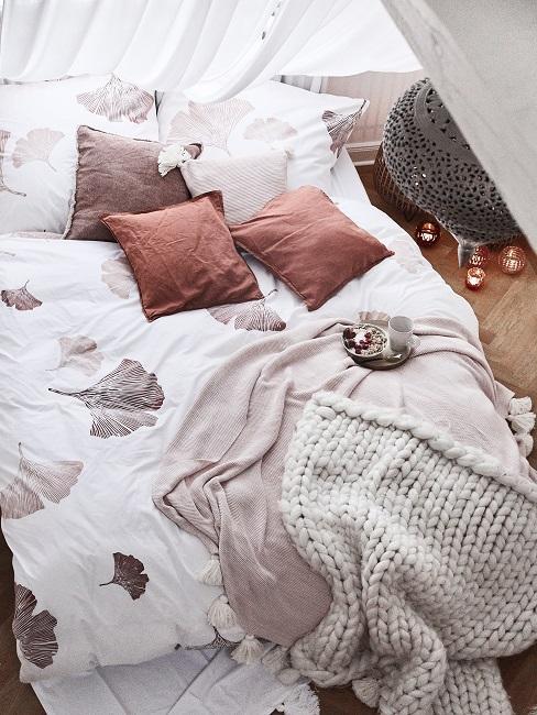 Bett mit gemusterter Bettwäsche aus ganzjährig verwendbarem Material mit Blattmuster