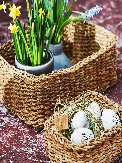 Körbe gefüllt mit Ostereiern und Blumentöpfen mit Narzissen