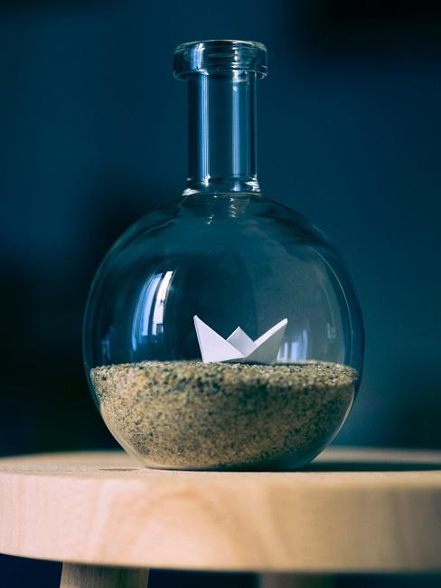 Eine leere Flasche als Deko auf einem Holz-Hocker, die mit Sand und einem kleinen Papier-Schiff maritim gestaltet ist