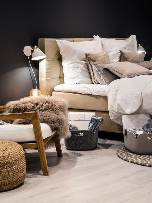 Schlafzimmer mit schwarzer Wand und beigem Boxspringbett, einem hellen Holzboden, einem Sessel neben dem Bett und Wandleuchten