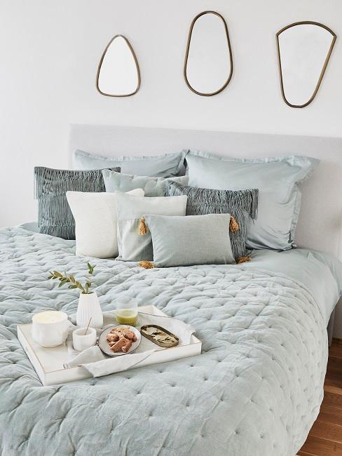 Großes Bett mit vielen dekorativen Kissen, einem Tablett und drei Spiegeln über dem Bettkopf als Wanddeko