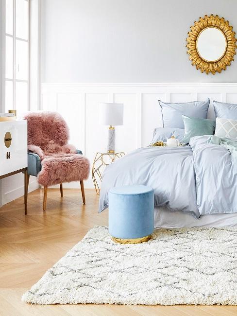 Großes Luxus Schlafzimmer mit einem XL Bett nahe des großen Fensters sowie luxuriösen goldfarbenen Accessoires