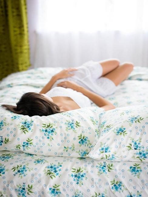 Frau liegt auf Bett mit geblümter Bettwäsche