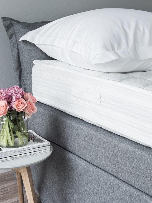 Matratze und Kissen auf Bett neben Beistelltisch