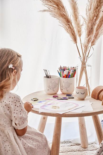 Mädchen sitzt an Tisch und malt