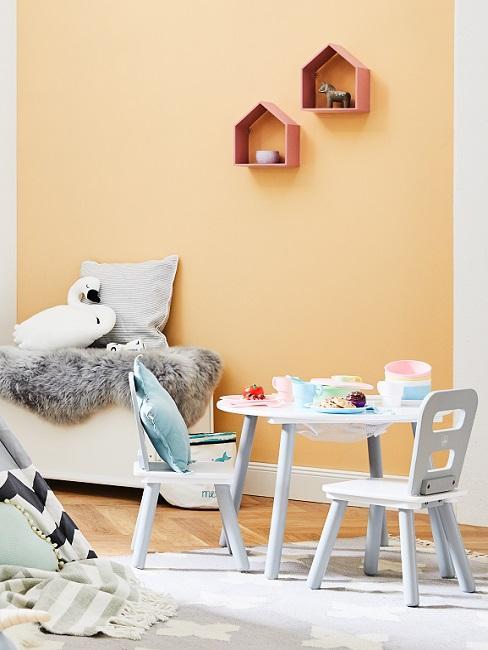 Apricotfarbene Wand im Babyzimmer mit weißen Möbeln und kuscheligen Textilien