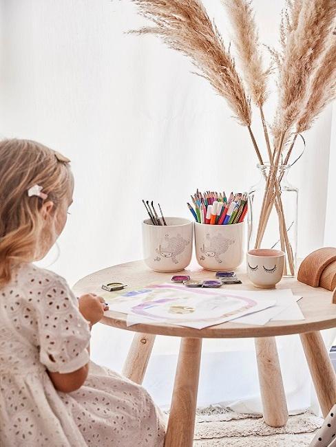 Mädchen sitzt am Tisch und malt