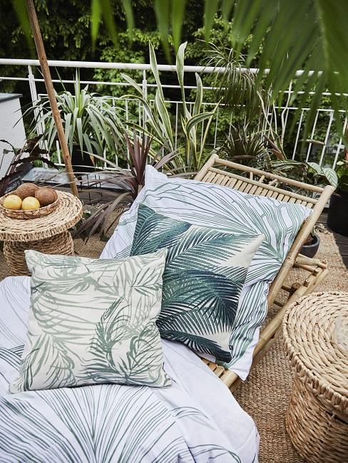 Grüne Dekokissen auf Sonnenliege neben Beistelltischen aus Bast