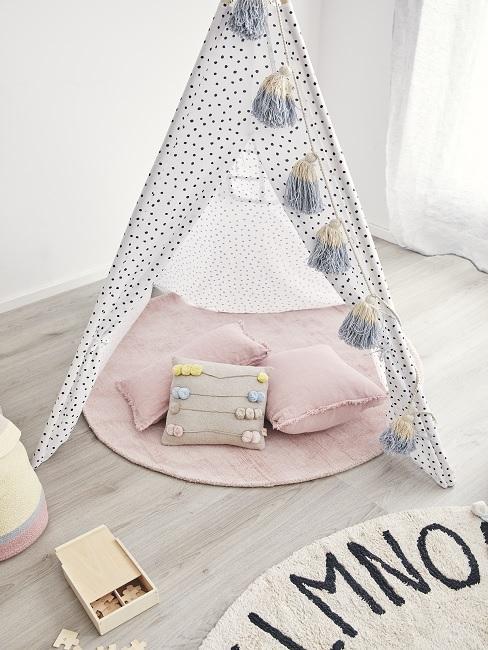 Tipi mit Kissen und Teppich als Kuschelecke im Kinderzimmer
