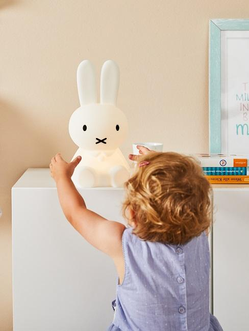 Baby mit Hasen-Tischleuchte in der Hand