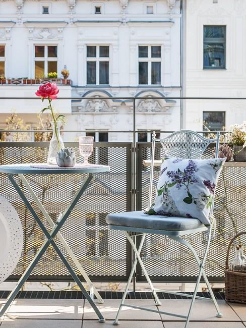 Schmalen Balkon gestalten mit Bistrostuhl und -tisch und blauen Kissen