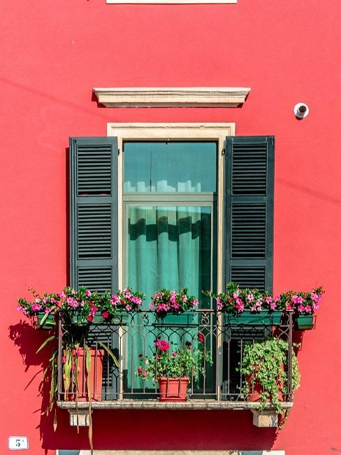 Französischer Balkon an roter Häuserfasse mit Pflanzendeko