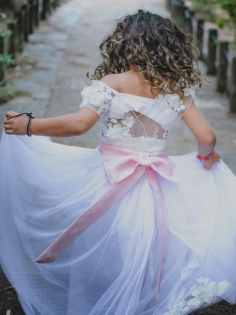 Mädchen in Taufkleid mit rosa Schleife