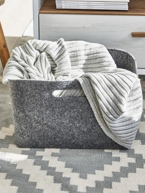 Ein beladener Wäschekorb in grau steht auf dem Teppich der Waschküche