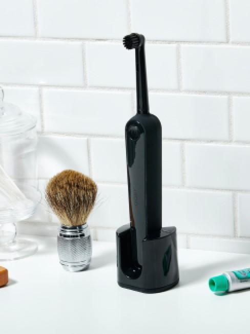 Schwarze elektrische Zahnbürste im Badezimmer reinigen