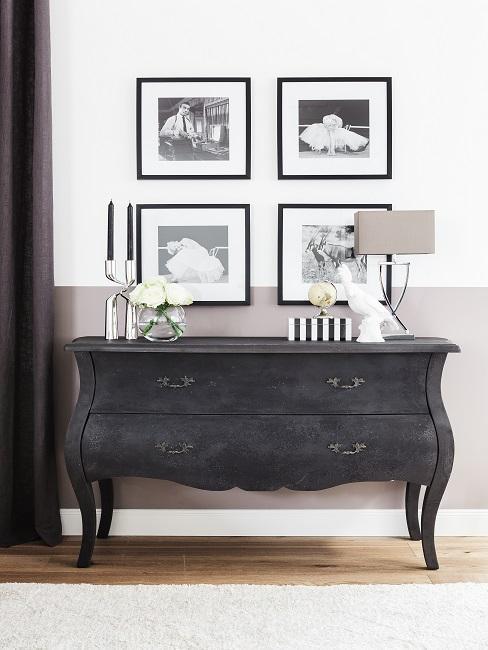 Cómoda de madera negra con lámpara y cuadros decorativos