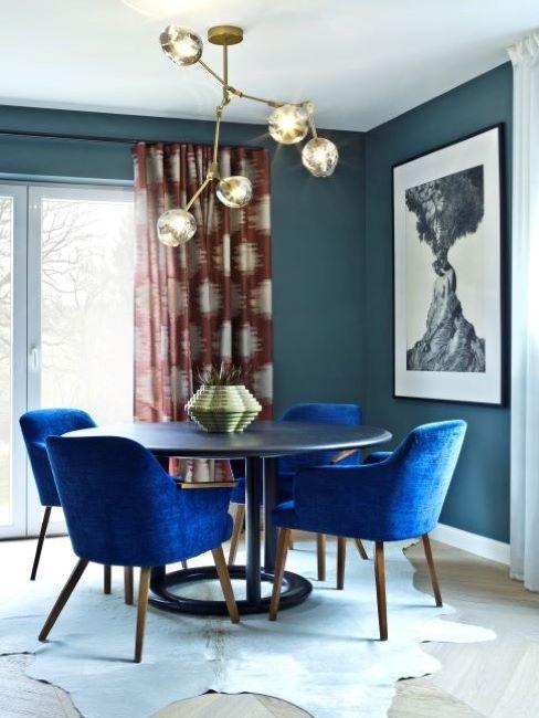 sala da pranzo classica con tavolo rotondo e sedie in velluto blu