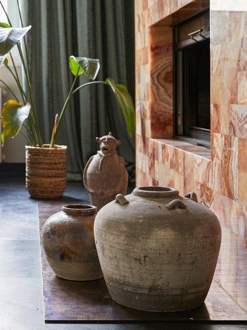 Marmeren haard met authentieke bruine potten en bananenplant in pot