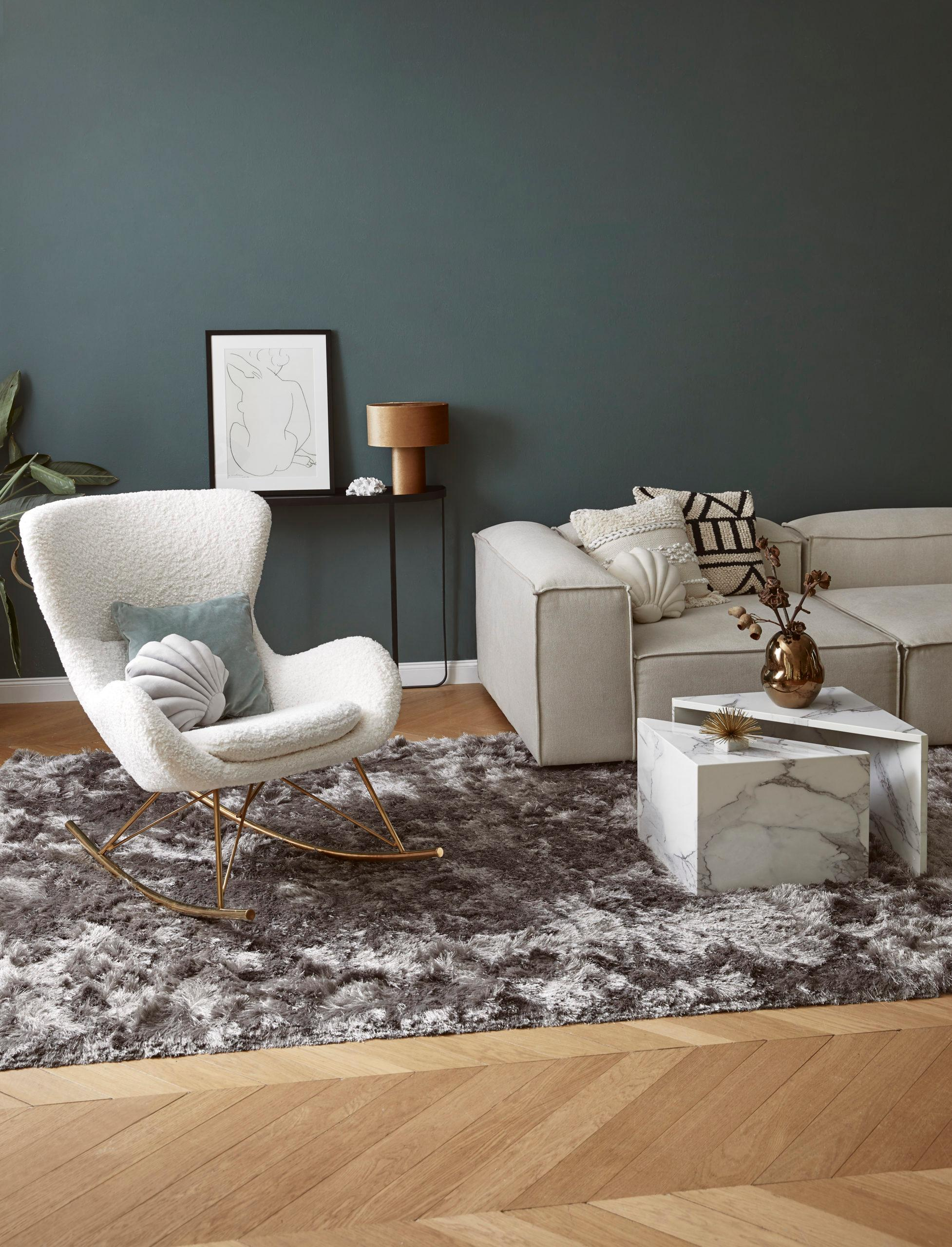 Grijsgroene muur met zandkleur bank en teddy stoel op taupe vloerkleed
