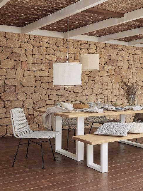 Stenen buitenruimte met wit houten tuinset met rotan gevlochten stoelen