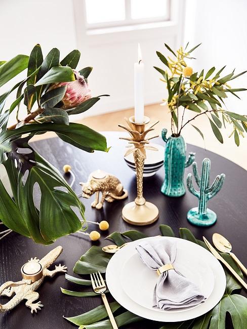 Czarny stół z dekoracjami zrobionymi z roślin oraz kwiatów