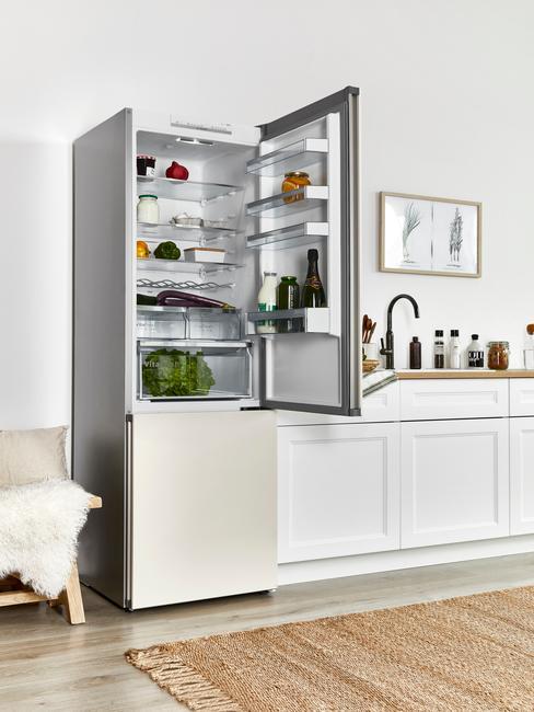 Jasna kuchnia ze srebrną lodówką z otwartymi drzwiami