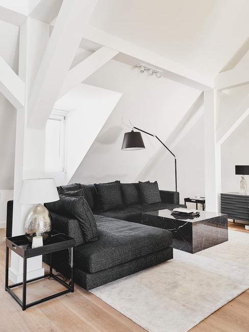 Szary szalon z dużą, narożną czarną kanapą, czarną lampą oraz stolikiem