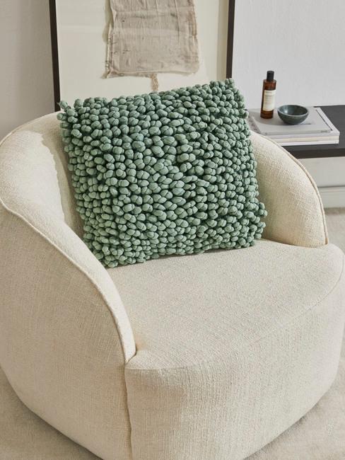 Poduszka w kolorze szałwiowej zieleni na beżowym fotelu