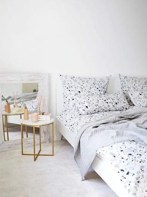 Biała sypialnia z łożkiem z białą pościelą i stolikiem o mosiążnych nóżkach