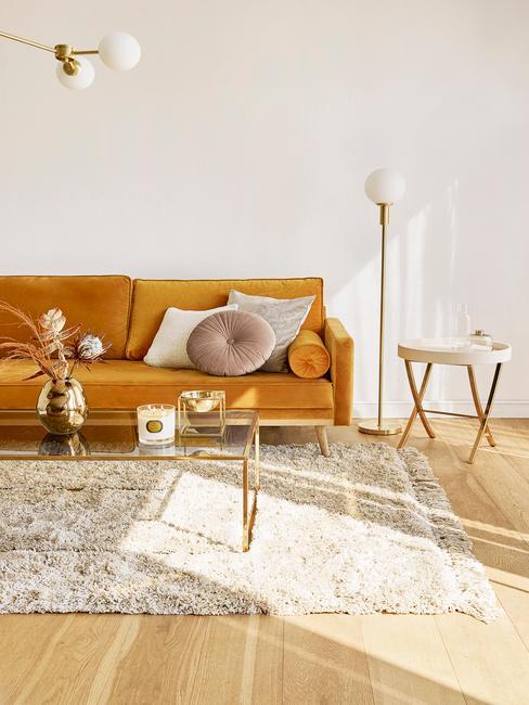 Sofa w kolorze ochry w białym salonie z dywanem, szklanym stolikem kawowym oraz dekoracjami