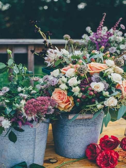 Kwiaty na stole weselnym w wiaderkach