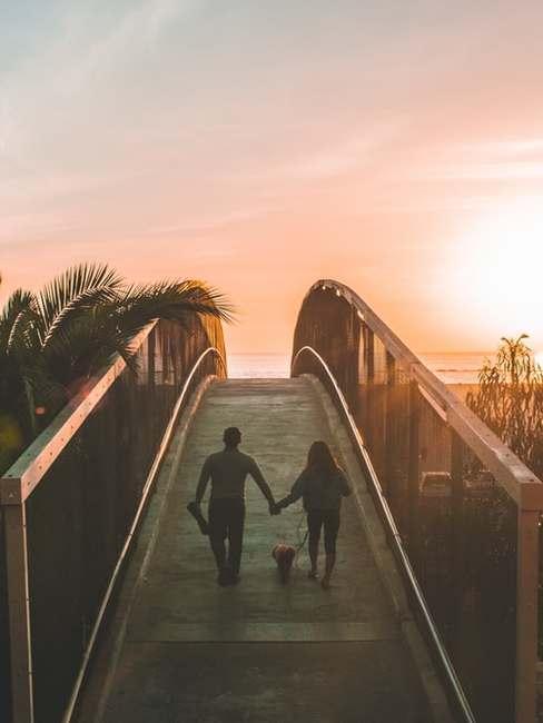 Dwie osoby idącez przez most przy zachodzie słońca