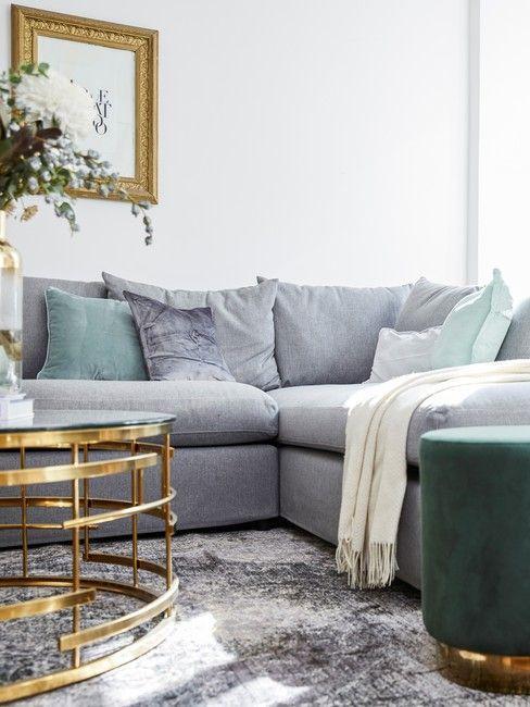 Miętowe poduszki na szarej sofie w salonie