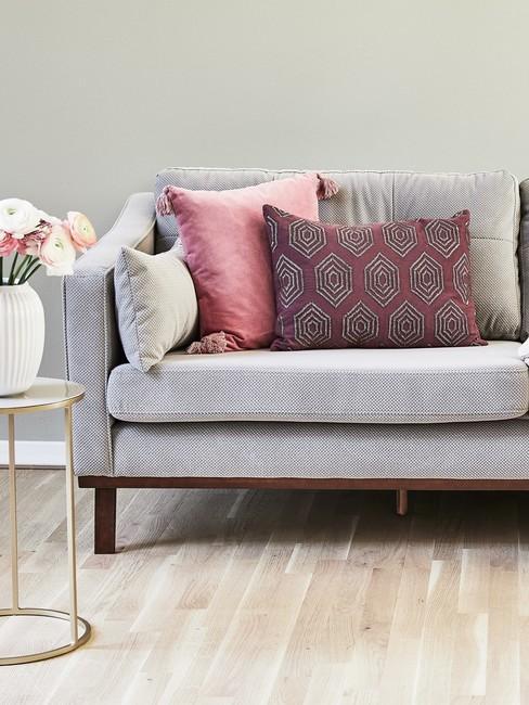 Salon z szarą sofą, fioletowymi poduszkami oraz białtym stolikiem z wazonem kwiatów