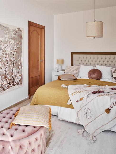 Sypialnia w stylu glam z podwójnym łóżkiem oraz różowym pufem