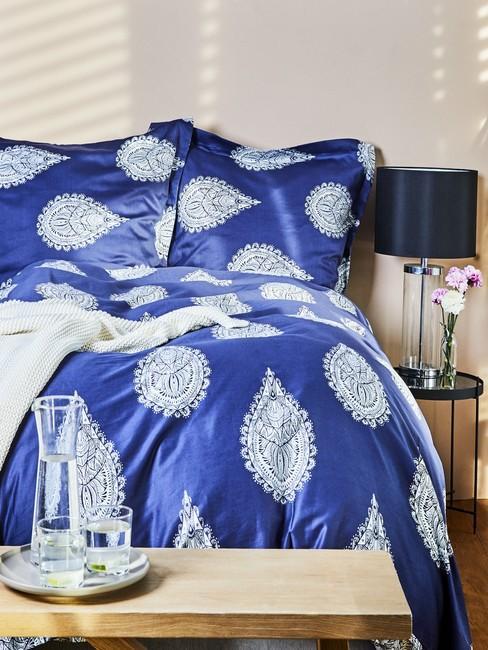 Sypialnia z pościelom z kobaltowym odcieniu oraz beżowymi ścianami