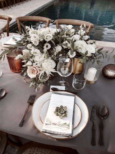 Stół na wesele w stylu boho z białą zastawą, niskim bukietem kwiatów oraz świecami