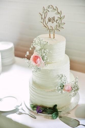 Prosty, klasyczny tort z delikatnymi kwiatami oraz napisem love
