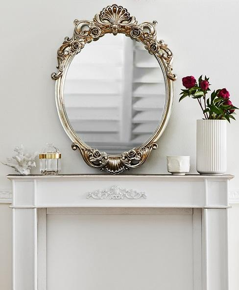 Lustro w srebrnej ramie położone na kominku obok białego wazonu z kwiatami
