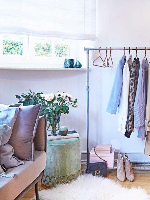 Wiesz na ubrania w pomieszczeniu z zielonym pufem oraz sofą z poduszkami