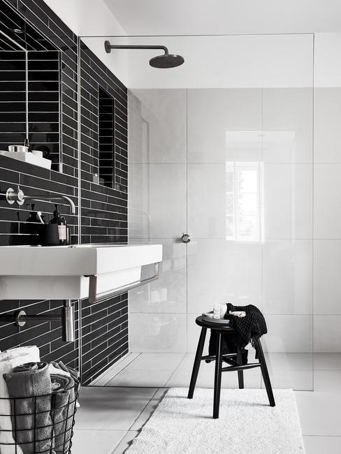 Czarno - biała łazienka z prysznicem, dużą umywalką oraz czarnym stołkiem